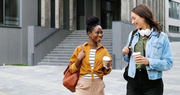Jonge mooie vrouwtjes van gemengde rassen, beste vrienden die vrolijk praten en wandelen met kopjes koffie om mee te nemen en op straat in de stad. multi-etnische stijlvolle gelukkige vrouwelijke studenten buiten wandelen met warme dranken