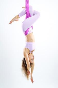 Jonge mooie yogivrouw die luchtyogapraktijk in purpere hangmat doen.