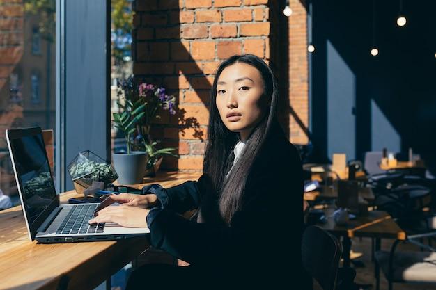 Jonge, mooie zakenvrouw aziatische freelancer die vanuit een restaurant op een laptop werkt die zelfverzekerd naar de camera in een pak kijkt
