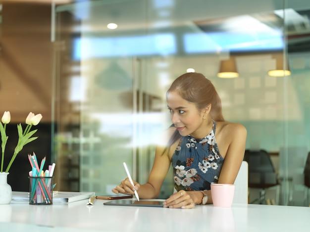 Jonge mooie zakenvrouw bezig met haar project in moderne kantoorruimte, uitzicht door glas