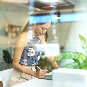 Jonge mooie zakenvrouw concentreren op haar project in moderne kantoorruimte, uitzicht door glas