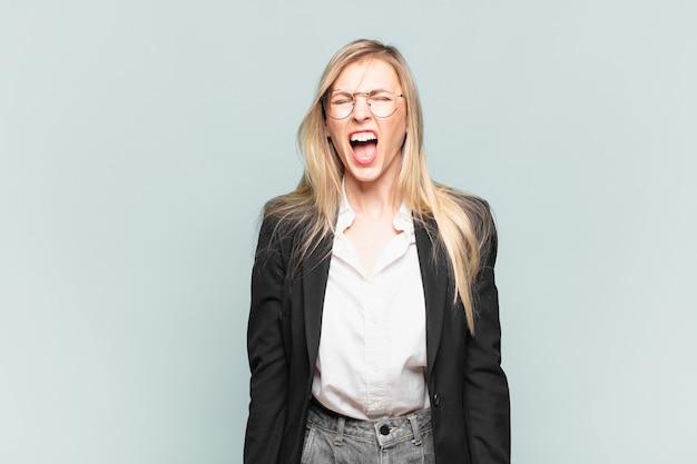 Jonge mooie zakenvrouw die agressief schreeuwt, erg boos, gefrustreerd, verontwaardigd of geïrriteerd kijkt, nee schreeuwt