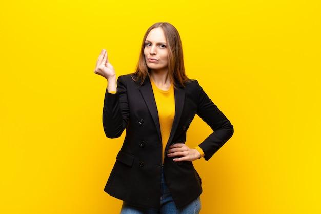 Jonge mooie zakenvrouw die capice of geldgebaar maakt en je zegt dat je je schulden moet betalen! tegen oranje muur