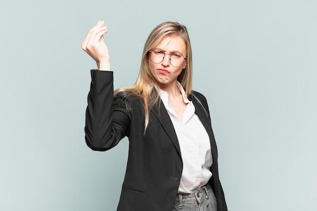Jonge mooie zakenvrouw die capice of geldgebaar maakt en u vertelt om uw schulden te betalen!