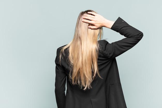 Jonge mooie zakenvrouw die denkt of twijfelt, hoofd krabt, zich verward en verward voelt, achter- of achteraanzicht