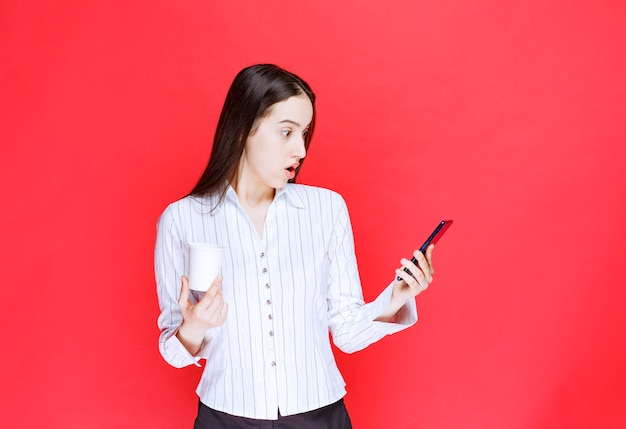 Jonge mooie zakenvrouw die een plastic beker vasthoudt en naar een mobiele telefoon kijkt.