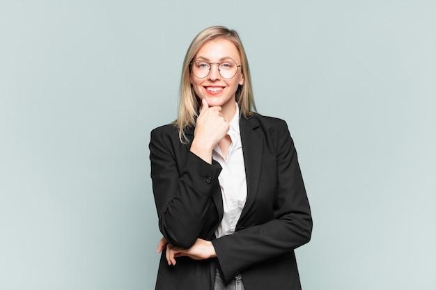 Jonge mooie zakenvrouw die er gelukkig uitziet en glimlacht met de hand op de kin, zich afvraagt of een vraag stelt, opties vergelijkt
