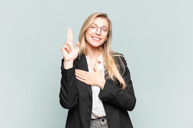 Jonge mooie zakenvrouw die er gelukkig, zelfverzekerd en betrouwbaar uitziet, glimlacht en een overwinningsteken toont, met een positieve houding