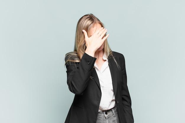 Jonge mooie zakenvrouw die er gestrest, beschaamd of overstuur uitziet, met hoofdpijn, gezicht bedekt met hand