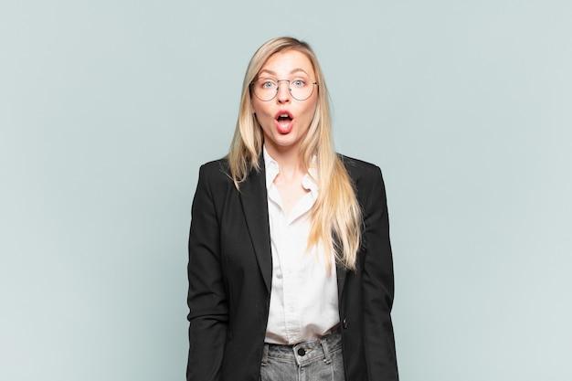 Jonge mooie zakenvrouw die erg geschokt of verrast kijkt, starend met open mond en zegt wow