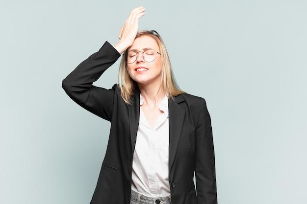 Jonge mooie zakenvrouw die handpalm naar voorhoofd steekt en denkt oeps, na een domme fout te hebben gemaakt of zich dom te voelen