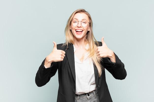 Jonge mooie zakenvrouw die in het algemeen lacht en er gelukkig, positief, zelfverzekerd en succesvol uitziet, met beide duimen omhoog