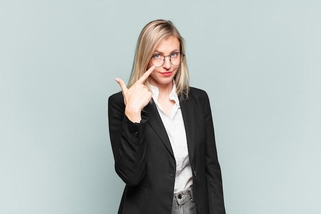 Jonge mooie zakenvrouw die je in de gaten houdt, niet vertrouwt, kijkt en alert en waakzaam blijft