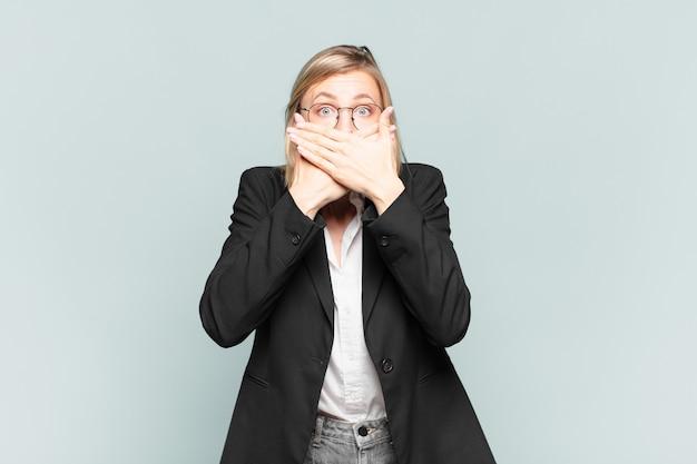 Jonge mooie zakenvrouw die mond bedekt met handen met een geschokte, verbaasde uitdrukking, een geheim houdt of oeps zegt