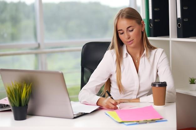 Jonge mooie zakenvrouw die op laptop in heldere moderne kantoor werkt