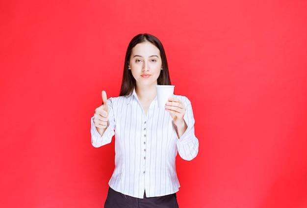 Jonge mooie zakenvrouw die plastic beker vasthoudt en duimen opgeeft.
