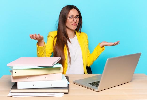 Jonge mooie zakenvrouw die verbaasd, verward en gestrest kijkt, zich afvraagt tussen verschillende opties, zich onzeker voelt