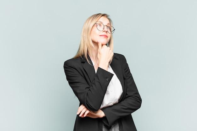 Jonge mooie zakenvrouw die zich nadenkend voelt, zich afvraagt of zich ideeën voorstelt, dagdroomt en omhoog kijkt om ruimte te kopiëren