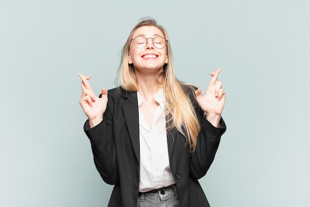 Jonge mooie zakenvrouw die zich nerveus en hoopvol voelt, vingers kruist, bidt en hoopt op geluk