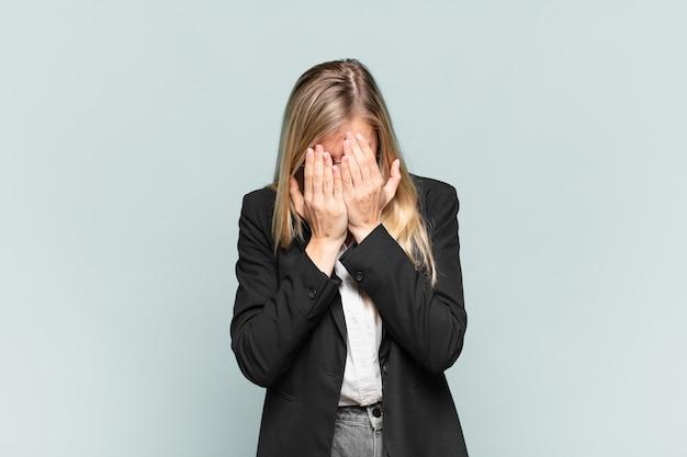 Jonge mooie zakenvrouw die zich verdrietig, gefrustreerd, nerveus en depressief voelt, gezicht met beide handen bedekt, huilend