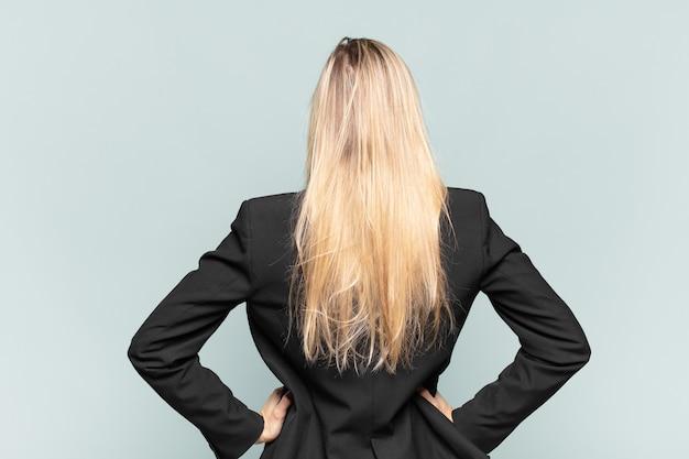 Jonge mooie zakenvrouw die zich verward of vol voelt of twijfels en vragen, zich afvragend, met de handen op de heupen, achteraanzicht