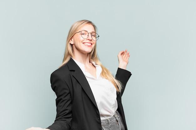 Jonge mooie zakenvrouw glimlacht, voelt zich zorgeloos, ontspannen en gelukkig, danst en luistert naar muziek, plezier op een feestje