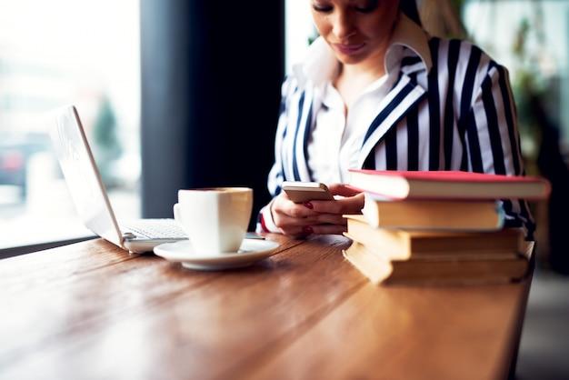 Jonge mooie zakenvrouw in een cafe het lezen van een sms-bericht van haar mobiel.