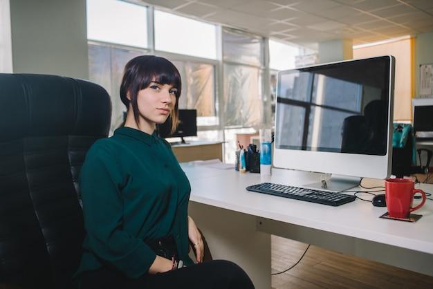 Jonge mooie zakenvrouw in een donkere jas zittend op de werkplek in de buurt van de computer in de bureaustoel.