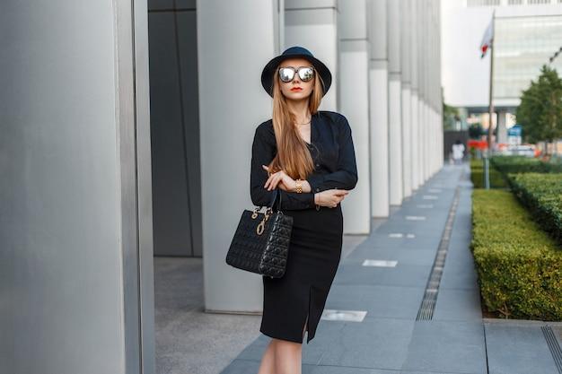 Jonge mooie zakenvrouw in zonnebril en hoed staande in de buurt van het moderne gebouw