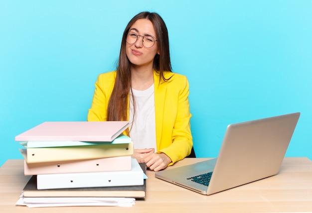 Jonge mooie zakenvrouw kijkt blij en vriendelijk, lacht en knipoogt naar je met een positieve houding