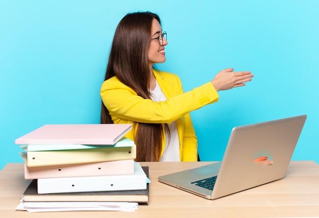 Jonge mooie zakenvrouw lacht, groet je en biedt een handdruk om een succesvolle deal, samenwerkingsconcept te sluiten