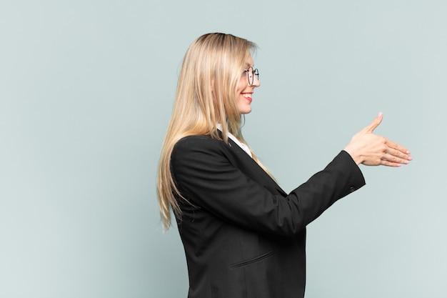 Jonge mooie zakenvrouw lacht, groet je en biedt een handdruk om een succesvolle deal te sluiten, samenwerkingsconcept