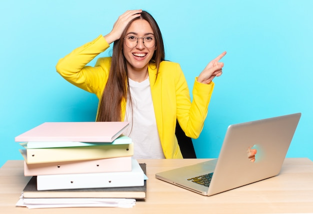 Jonge mooie zakenvrouw lacht, kijkt blij, positief en verrast, realiseert zich een geweldig idee wijzend naar laterale kopie ruimte