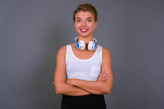 Jonge mooie zakenvrouw met blond haar koptelefoon dragen op grijs