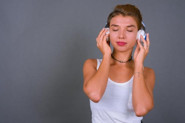Jonge mooie zakenvrouw met blond haar, luisteren naar muziek op grijs