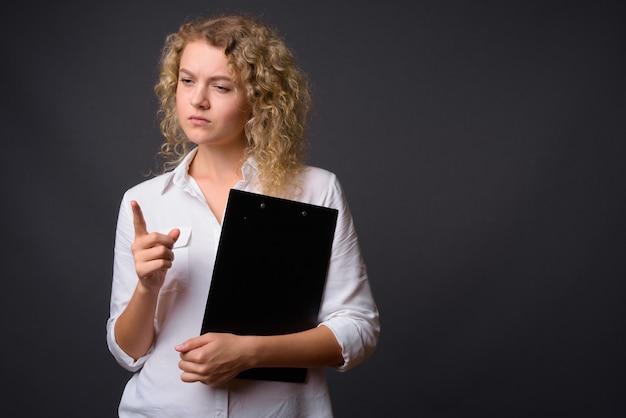 Jonge mooie zakenvrouw met krullend blond haar met klembord