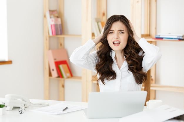 Jonge mooie zakenvrouw met laptop en document in het heldere moderne kantoor binnenshuis