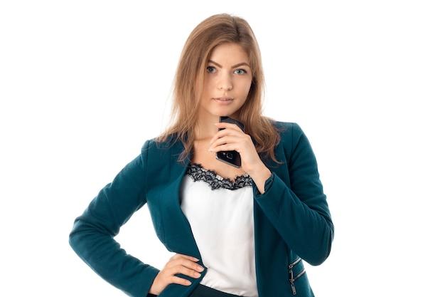 Jonge mooie zakenvrouw met mobiele telefoon in hand in blauwe jas kijken naar de camera geïsoleerd op witte backround