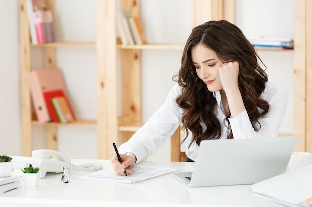 Jonge mooie zakenvrouw met notitieboekje en document in het heldere, moderne kantoor binnenshuis