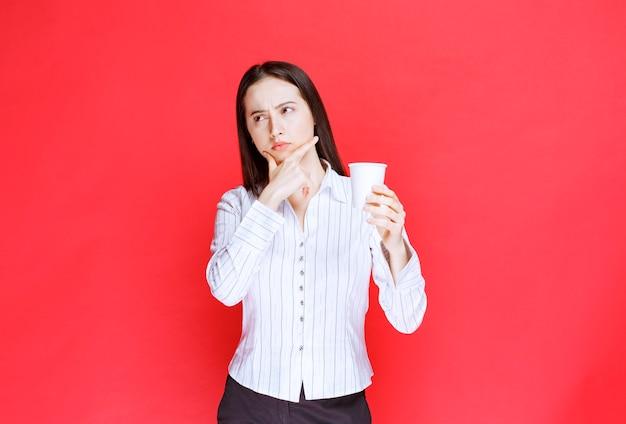 Jonge mooie zakenvrouw met plastic beker op rode achtergrond.
