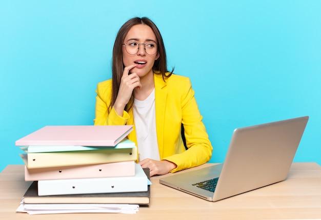 Jonge mooie zakenvrouw met verbaasde, nerveuze, bezorgde of angstige blik, opzij kijkend naar kopie ruimte