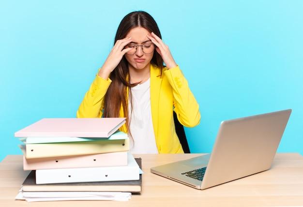 Jonge mooie zakenvrouw op zoek gestrest en gefrustreerd, werkt onder druk met hoofdpijn en last van problemen