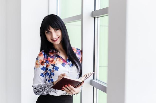 Jonge mooie zakenvrouw permanent in de buurt van het venster, schrijven in een notitieblok, kijken naar de camera glimlachen.