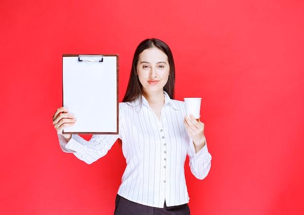 Jonge mooie zakenvrouw poseren met lege klembord en plastic beker.