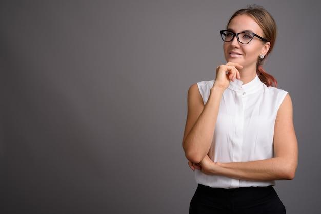 Jonge mooie zakenvrouw tegen de grijze muur