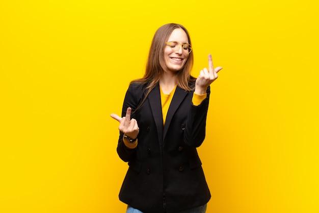 Jonge mooie zakenvrouw voelt provocerend, agressief en obsceen, flipping de middelvinger, met een opstandige houding tegen oranje muur