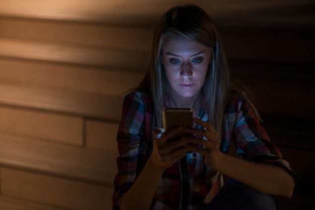 Jonge mooie zakenvrouw zitten 's nachts lichten met mobiele slimme telefoon. avondvrouw die op afstand werkt. surfen internetcursussen, boeken lezen, online video kijken, sms-bericht.