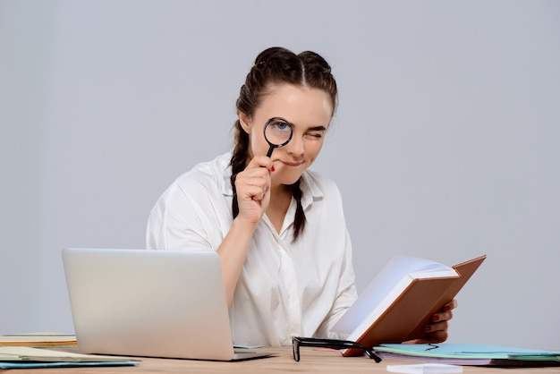 Jonge mooie zakenvrouw zittend op de werkplek, met boek en vergrootglas