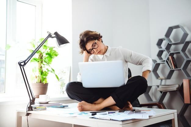 Jonge mooie zakenvrouw zittend op tafel met laptop op de werkplek.