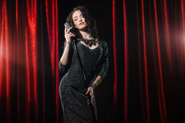 Jonge mooie zanger in zwarte jurk poseren met microfoon